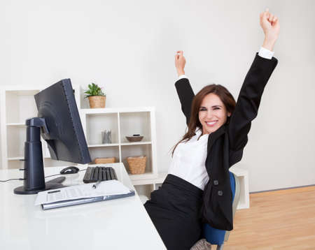 cheering: Portrait of Cheering Businesswoman At Desk In Office. Stock Photo