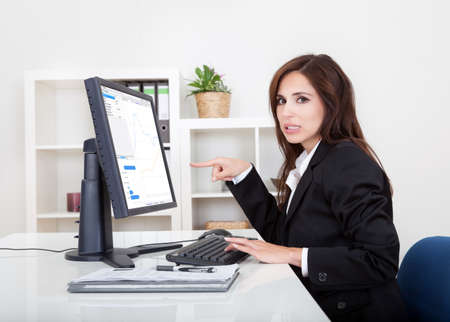 Businesswoman Showing Graph On Monitor In Office. photo