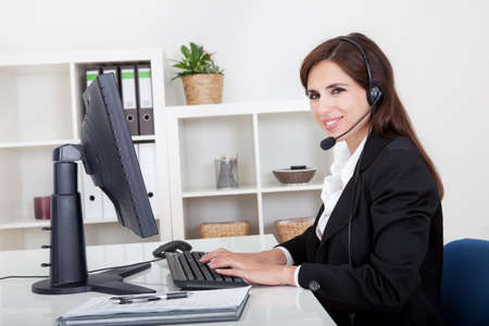 Young Cheerful Smiling Support Phone Female Operator In Headset At Office. photo