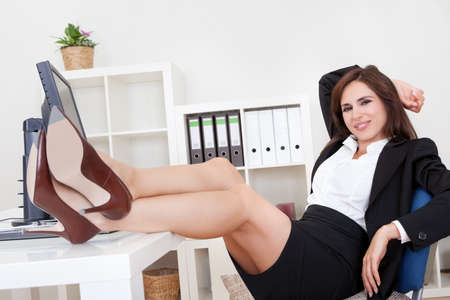 Young Businesswoman With Her Legs On The Desk. photo
