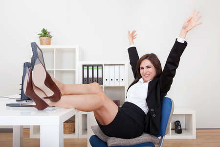 at her desk: Young Businesswoman With Her Legs On The Desk.