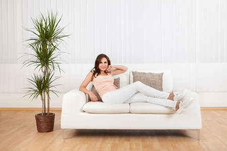 Portrait Of Young Woman Relaxing On Sofa At Home. photo