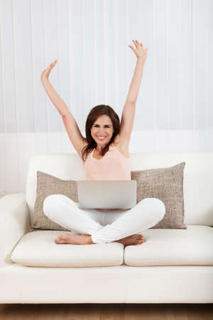 woman typing: Happy Woman Sitting On The Sofa Using Laptop.