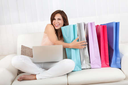home shopping: Woman Sitting On Sofa Holding Shopping Bag At Home.