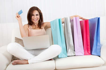 woman shopping: Young Woman Sitting On Sofa Shopping Online With Shopping Bags.