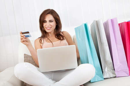 Young Woman Sitting On Sofa Shopping Online With Shopping Bags. photo