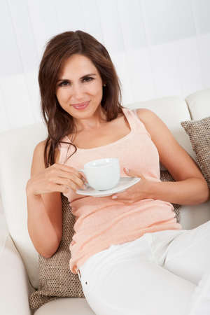 Portrait Of Young Woman Sitting On Sofa Drinking Coffee. photo