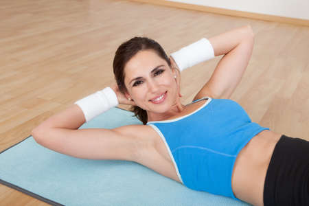 strengthen: Attractive happy woman lying on a mat working out doing lift ups to strengthen her abdominal muscles