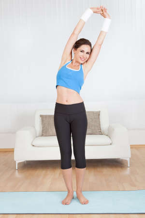 arm extended: Young woman stretching her muscles at home Stock Photo