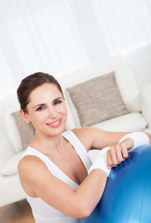 Close up of a happy smiling woman with a large blue pilates ball in a health and fitness concept photo
