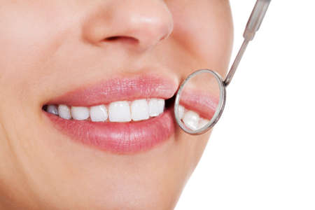 Cropped view of the mouth of a smiling woman with perfect white teeth and a small dentists mirror reflecting her teeth being held alongside Stock Photo - 15133519