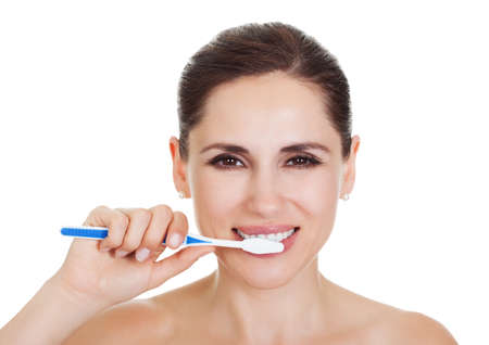 Beautiful smiling woman cleaning her teeth with a toothbrush in a dental hygiene concept. Isolated on white Stock Photo - 15493526