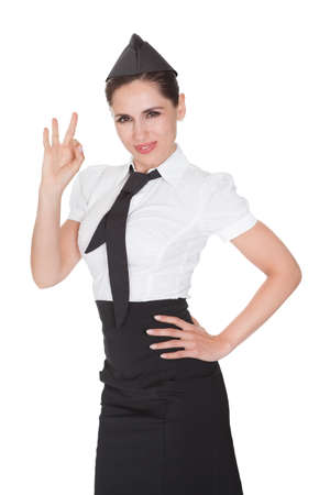 Beautiful sophisticated stylish stewardess making Ok hand gesture. Isolated on white photo