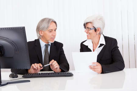 Smiling senior partners sitting together at a desk having a business meeting Stock Photo - 15493578