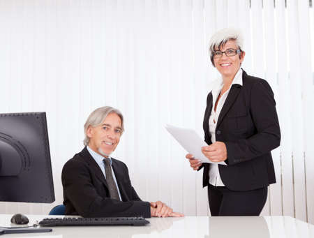 A senior business executive seated at his desk and his secretary or personal assistant photo