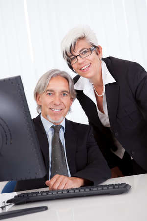 Smiling senior partners sitting together at a desk having a business meeting Stock Photo - 15493466