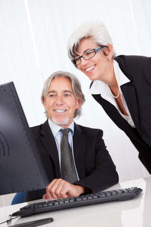 Smiling senior partners sitting together at a desk having a business meeting Stock Photo - 15493504