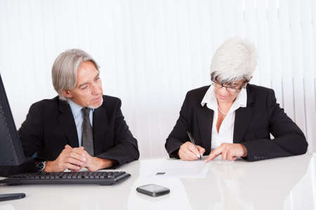 Smiling senior partners sitting together at a desk having a business meeting Stock Photo - 15493546