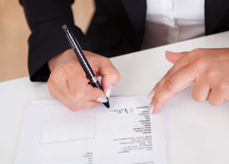 Cropped view image of female hands signing a document with a ballpoint pen Stock Photo - 15133641