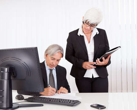 personal assistant: A senior business executive seated at his desk signs a document that has been brought to him by his secretary or personal assistant