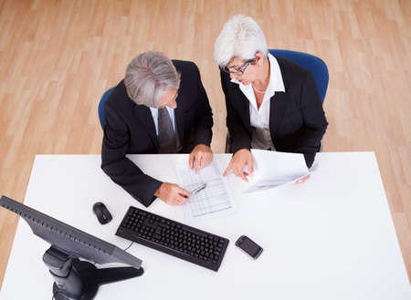 topdown: Smiling senior partners sitting together at a desk having a business meeting Stock Photo