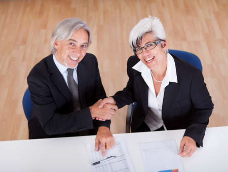 Overhead view of business handshake sealing a deal between two smiling senior businesspeople seated at a table photo