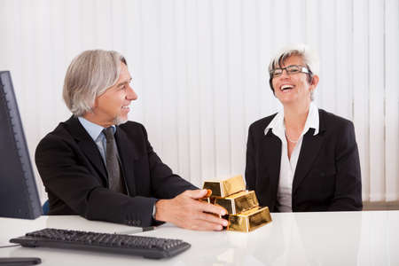 gleeful: Gleeful businesswoman grabbing hold of a stack of gold bullion bars as she reaps the rewards for astute business practices and investments