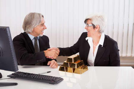 company ownership: Gleeful businesswoman grabbing hold of a stack of gold bullion bars as she reaps the rewards for astute business practices and investments