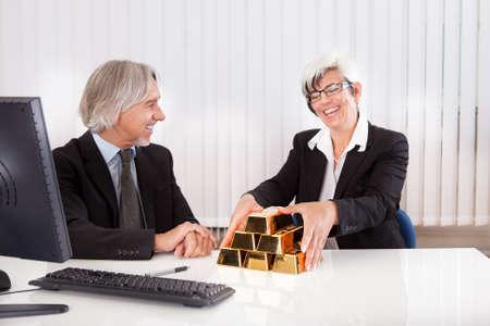lingotes de oro: Empresaria alegre agarrándose de una pila de lingotes de oro como se ve recompensado por prácticas empresariales astutos e inversiones Foto de archivo