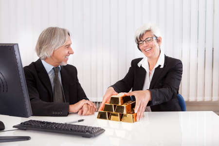 bullion: Gleeful businesswoman grabbing hold of a stack of gold bullion bars as she reaps the rewards for astute business practices and investments