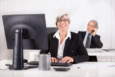 personal assistant: Smiling secretary or personal assistant sitting working at her desk with her boss visible on the telephone in the background