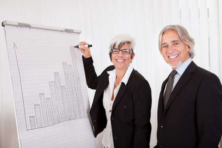 Businesswoman giving a presentation to her male colleague drawing a bar graph on a board as they analyze performance and discuss strategy photo