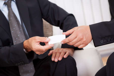 credentials: Business card being passed over between a male and female businessperson in suits