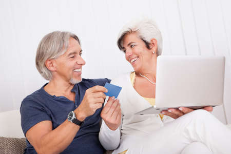 Happy attractive middle-aged couple making an online purchase or booking using a credit card on their laptop photo