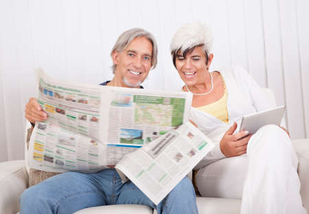 Senior couple sitting close together on a sofa sharing a newspaper as they catch up on the days news photo
