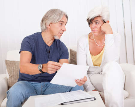 unfavorable: Attractive senior couple sitting on a sofa discussing a document with pessimistic looks on their faces