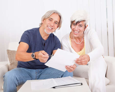 Excited middle-aged couple sitting on a couch reading a document together which contains good news photo