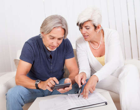 adds: Senior couple doing their finances with the woman checking the accounts while the husband adds up the figures on the calculator