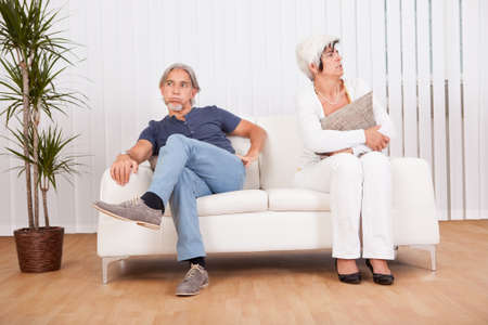 withdrawn: Senior couple after an argument sitting at opposite ends of the sofa sulking and looking away from each other into the distance Stock Photo