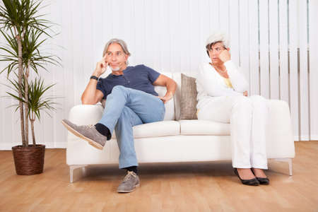 introspective: Senior couple after an argument sitting at opposite ends of the sofa sulking and looking away from each other into the distance Stock Photo