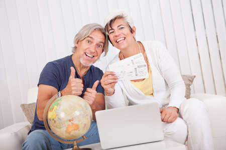 Ecstatic senior couple giving a thumbs up of success and victory as they display the tickets for their vacation photo