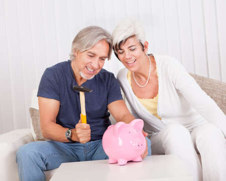 nestegg: Senior couple raiding a piggybank sitting with a hammer in the mans hand and looks of anticipation and glee Stock Photo