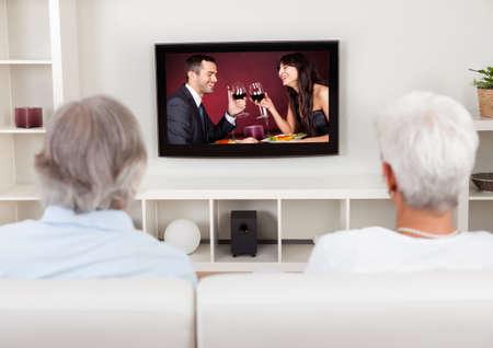 personas viendo tv: Vista trasera de una pareja viendo la televisi�n con una escena en la pantalla de un hombre y una mujer j�venes celebrando Foto de archivo