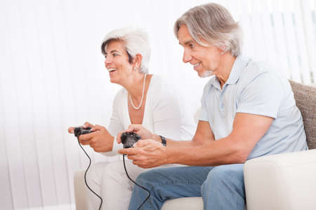 concentrating: Excited middle-aged couple sitting on a sofa in their living room in front of the television screen playing computer games