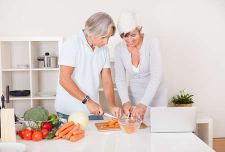 High angle view of an attractive middle-aged couple preparing a meal chopping vegetables in their kitchen photo