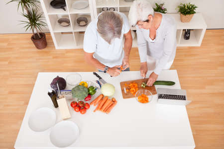 chopping: High angle view of an attractive middle-aged couple preparing a meal chopping vegetables in their kitchen