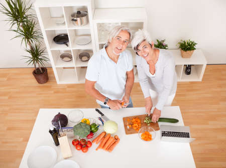 topdown: High angle view of an attractive middle-aged couple preparing a meal chopping vegetables in their kitchen