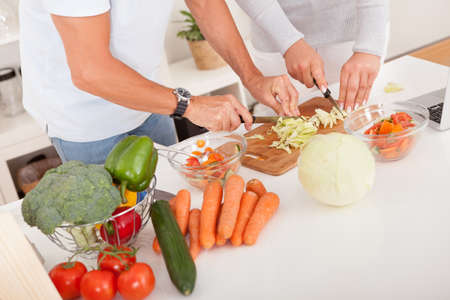 meal preparation: High angle view of an attractive middle-aged couple preparing a meal chopping vegetables in their kitchen