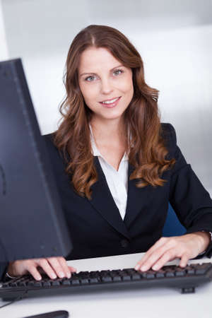 personal assistant: Smiling professional business secretary or personal assistant working at her computer typing on the keyboard Stock Photo