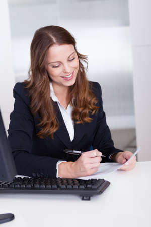 Smiling businesswoman working at her computer in the office Stock Photo - 15175658